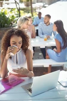 Mooie vrouw die mobiele telefoon met behulp van terwijl het hebben van koffie