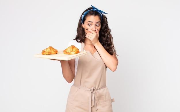Mooie vrouw die mond bedekt met handen met een geschokte en een croissantsdienblad vasthoudt