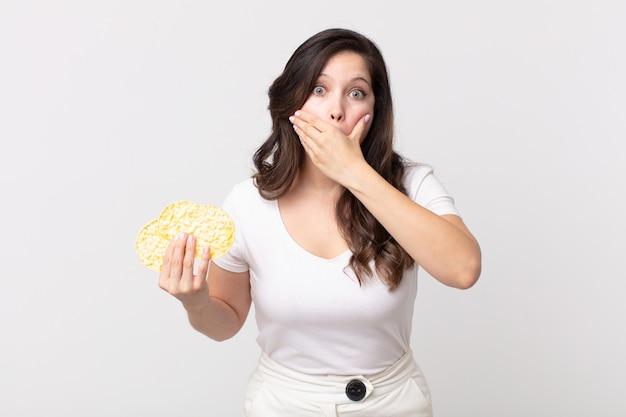 Mooie vrouw die mond bedekt met handen met een geschokte en een dieetrijstwafels vasthoudt