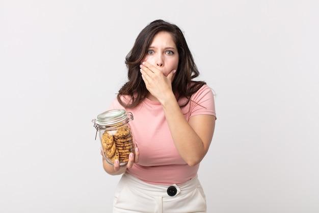 Mooie vrouw die mond bedekt met handen met een geschokte en een glazen fles met koekjes vasthoudt