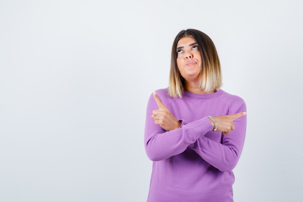 Mooie vrouw die naar beide kanten wijst, omhoog kijkt in een paarse trui en besluiteloos kijkt. vooraanzicht.