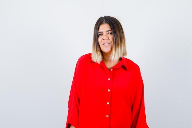Mooie vrouw die naar de camera in een rode blouse kijkt en er verstandig uitziet. vooraanzicht.