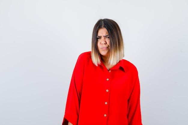 Mooie vrouw die naar de camera kijkt terwijl ze fronst in een rode blouse en peinzend kijkt. vooraanzicht.