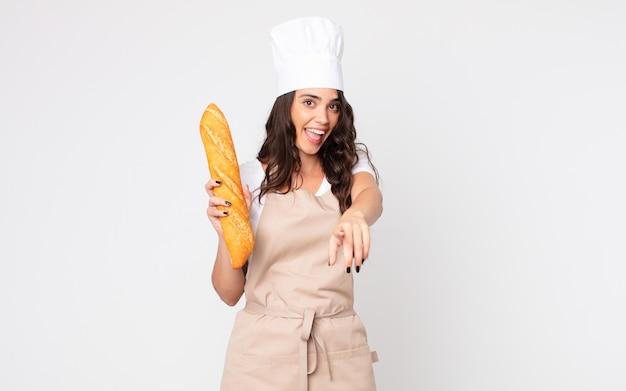 Mooie vrouw die naar de camera wijst en ervoor kiest dat je een schort draagt en een stokbrood vasthoudt
