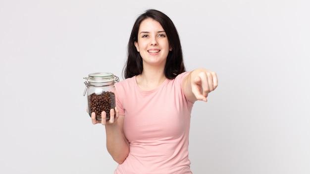 Mooie vrouw die naar de camera wijst en jou kiest en een fles koffiebonen vasthoudt