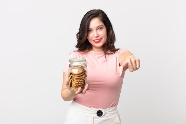 Mooie vrouw die naar de camera wijst en jou kiest en een glazen fles met koekjes vasthoudt