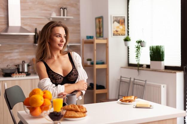 Mooie vrouw die naar de voorkant in de keuken kijkt en sexy lingerie draagt