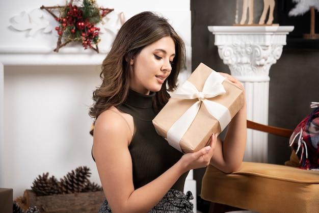 Mooie vrouw die naar een speciaal kerstcadeau kijkt