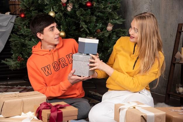 Mooie vrouw die naar haar vriendje kijkt en hem cadeautjes geeft in het interieur.