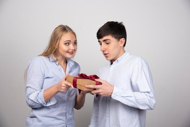 Mooie vrouw die naar haar vriendje kijkt en hem een cadeau geeft op een grijze muur.