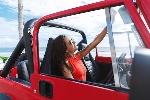 Mooie vrouw die naar het strand in zwempak gaat, in auto zit en neemt selfie op zonnige dag dichtbij overzees.