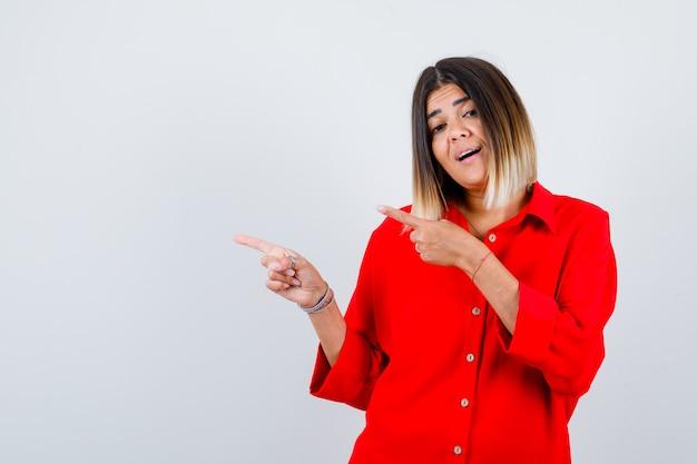 Mooie vrouw die naar links wijst in een rode blouse en zich afvraagt, vooraanzicht.