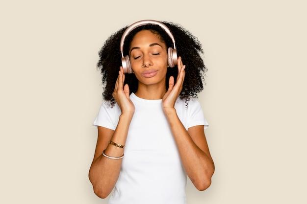 Mooie vrouw die naar muziek luistert via een digitaal hoofdtelefoonapparaat