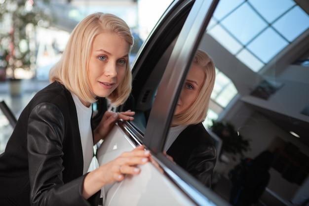 Mooie vrouw die nieuwe auto voor verkoop onderzoeken bij handel drijven salon