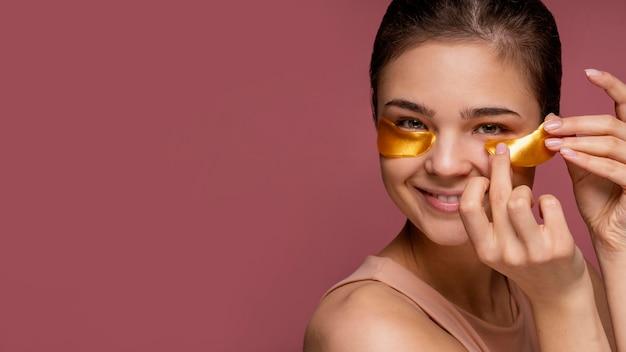 Mooie vrouw die onder de maskers van het oogflard gebruikt