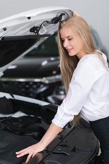 Mooie vrouw die onder motorkap van auto kijkt