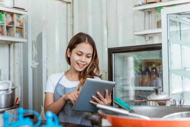 Mooie vrouw die online bestelling neemt bij haar kleine stalletje. jonge eigenaar van een klein bedrijf