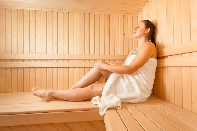 Mooie vrouw die op bank bij scandinavische sauna ligt