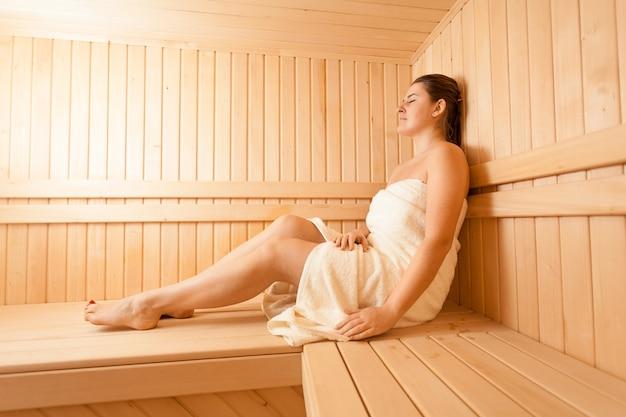 Mooie vrouw die op bank bij traditionele sauna ligt