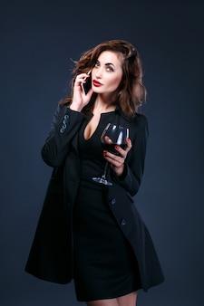 Mooie vrouw die op cel spreekt terwijl het houden van glaswijn