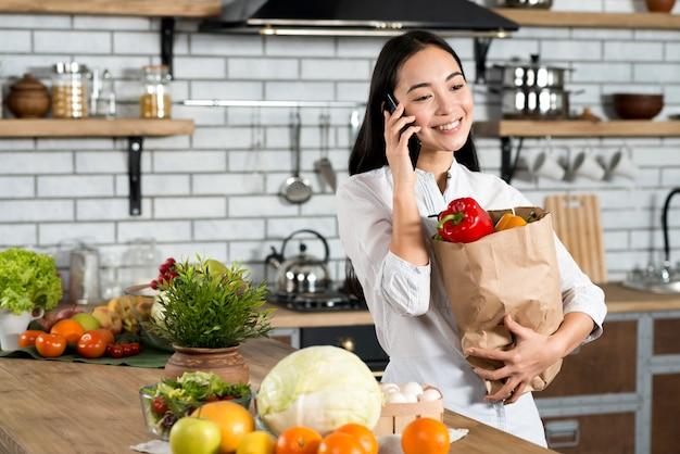 Mooie vrouw die op cellphone spreekt die bruine plantaardige zak houdt