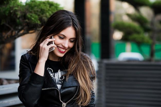 Mooie vrouw die op cellulaire telefoon spreekt openlucht