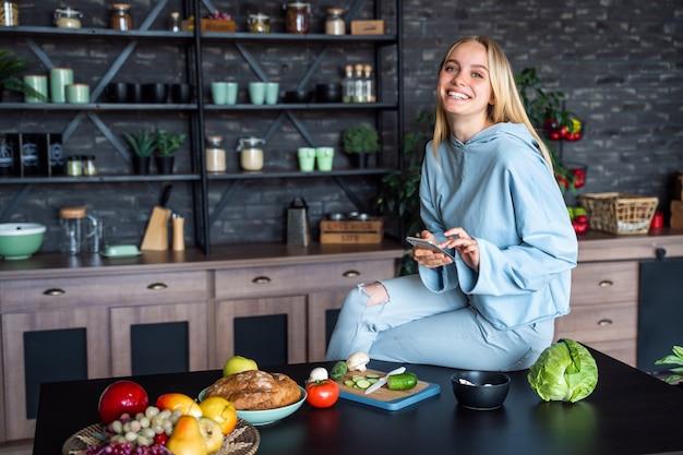 Mooie vrouw die op de mobiele telefoon in keuken thuis spreekt