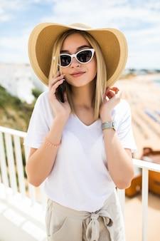 Mooie vrouw die op de reling van het terras leunt, ontspant en een telefoontje heeft