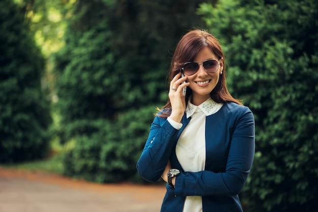 Mooie vrouw die op de telefoon in het stadspark spreekt
