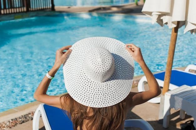 Mooie vrouw die op een strand bij tropische reistoevlucht zonnebaden, die van de zomervakantie genieten