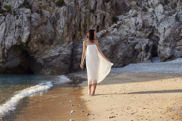 Mooie vrouw die op een strand loopt