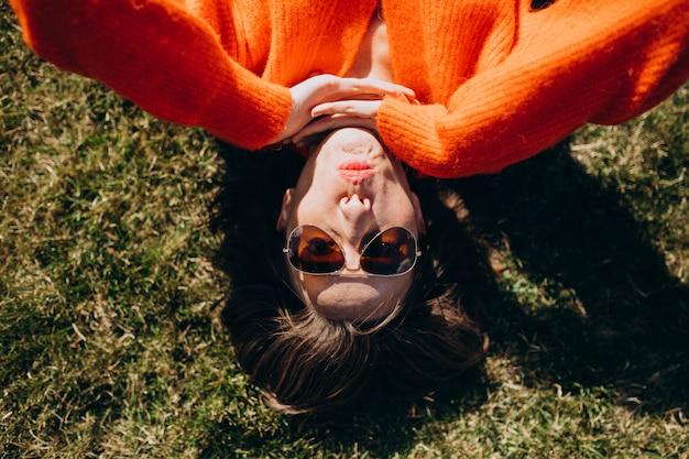 Mooie vrouw die op gras in een kleurrijke sweater ligt