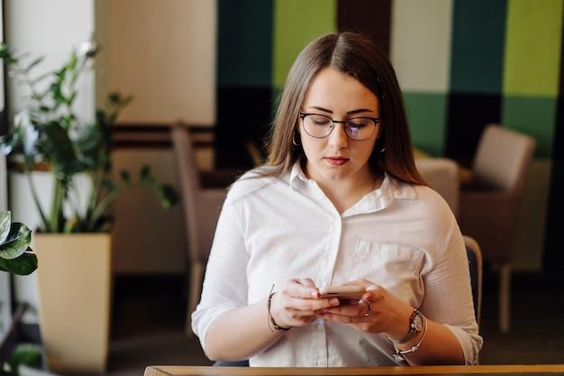 Mooie vrouw die op haar laptop en telefoon aan een stijlvol stedelijk restaurant werkt