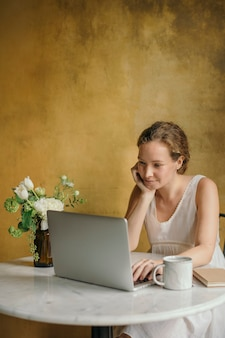 Mooie vrouw die op haar laptop werkt in een café
