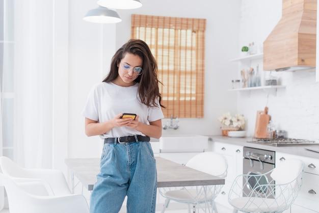 Mooie vrouw die op haar telefoon kijkt