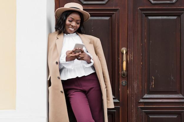 Mooie vrouw die op haar telefoon met exemplaarruimte kijkt