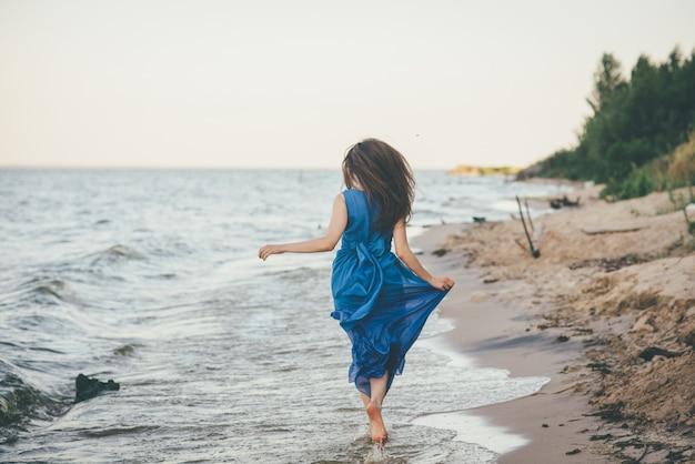 Mooie vrouw die op het strand in het water loopt