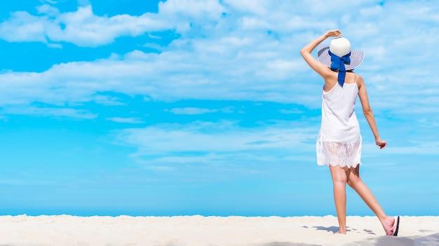 Mooie vrouw die op het strand met blauwe hemel loopt. fijne zomervakantie.