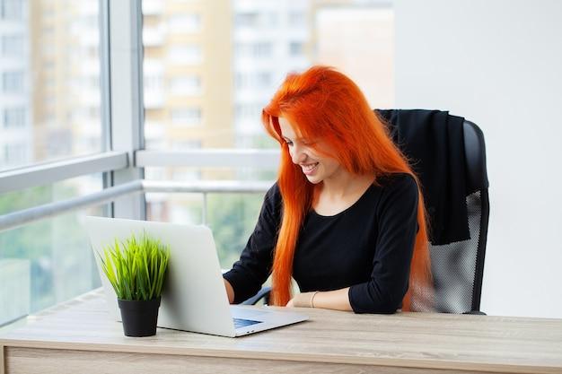 Mooie vrouw die op laptop op kantoor werkt.