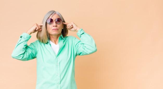 Mooie vrouw die op middelbare leeftijd zonnebril draagt tegen muur