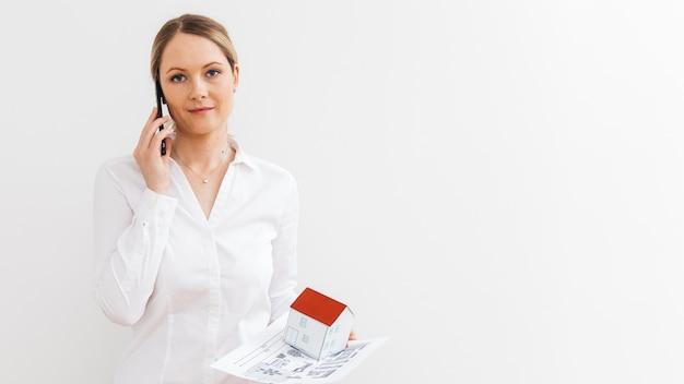 Mooie vrouw die op smartphone met holdingsblauwdruk en miniatuurhuismodel spreekt over witte muur