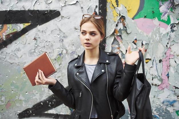Mooie vrouw die op straat loopt met een notitieboekje in haar handen, mode moderne stijl