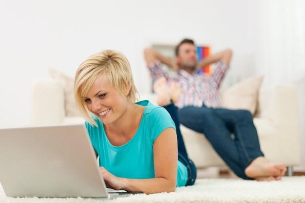 Mooie vrouw die op tapijt ligt en laptop met behulp van