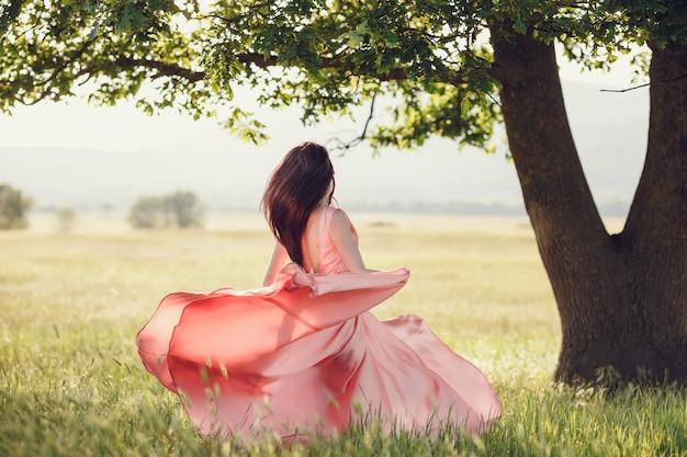 Mooie vrouw die op tarwegebied loopt vóór zonsondergang