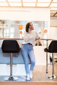 Mooie vrouw die op telefoon spreekt die zich in panoramische keuken met heldere muren hoge lijst en barstoelen bevindt