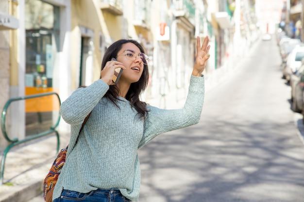 Mooie vrouw die op telefoon spreekt en voor taxi begroet