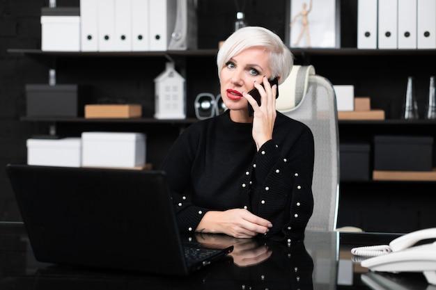 Mooie vrouw die op telefoonzitting bij lijst in bureau spreekt