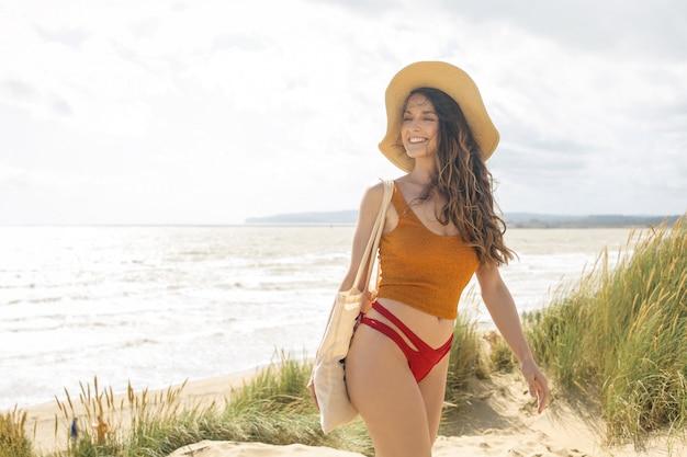 Mooie vrouw die op zandduin bij het strand loopt
