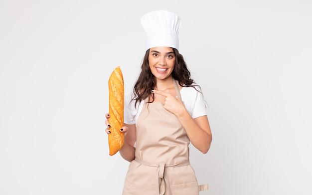 Mooie vrouw die opgewonden en verrast kijkt en naar de zijkant wijst met een schort en een stokbrood vasthoudt