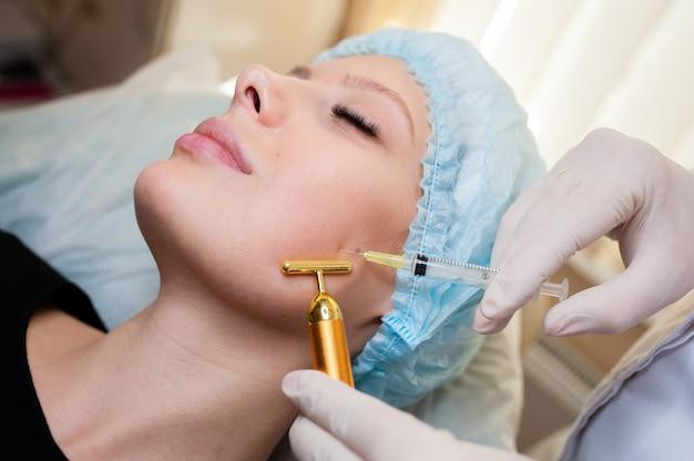Mooie vrouw die opheffende injectie in jukbeenderen krijgt. injecties van huidverjonging. cosmetische procedures, injecties.